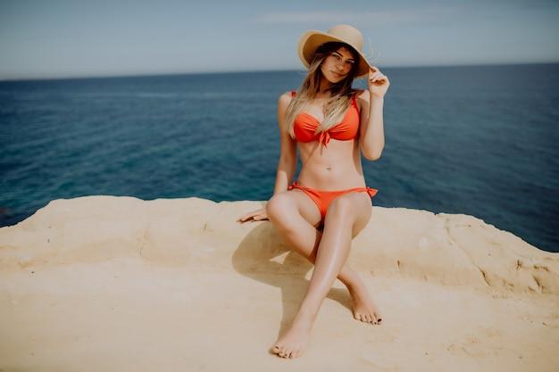 Młoda kobieta w słomkowym kapeluszu i bikini siedzi na końcu skały
