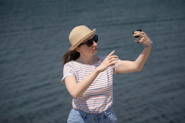 Młoda kobieta w słomkowym kapeluszu i okularach przeciwsłonecznych robi selfie kamerą sportową na jeziorze...