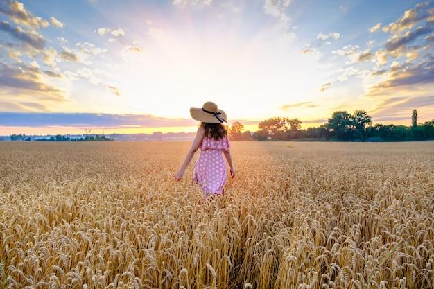 Młoda kobieta w słomkowym kapeluszu na głowie idzie przez pole pszenicy z powrotem do kamery na wschód słońca. skopiuj miejsce