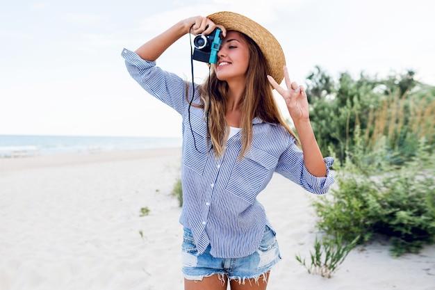 Młoda kobieta w słomkowym kapeluszu robi zdjęcie aparatem retro na plaży