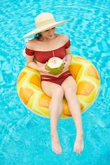 Młoda kobieta w słomkowym kapeluszu siedzi na dmuchanym ringu w basenie i pije kokosowy koktajl