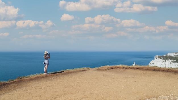 Młoda kobieta w słomkowym kapeluszu stojąca na wzgórzu nad morzem, robiąca zdjęcie zapierającego dech w piersiach krajobrazu podczas podróży etretat normandia francja