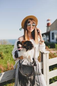Młoda kobieta w słomkowym kapeluszu z psem przy płocie na wsi rozmawia przez telefon