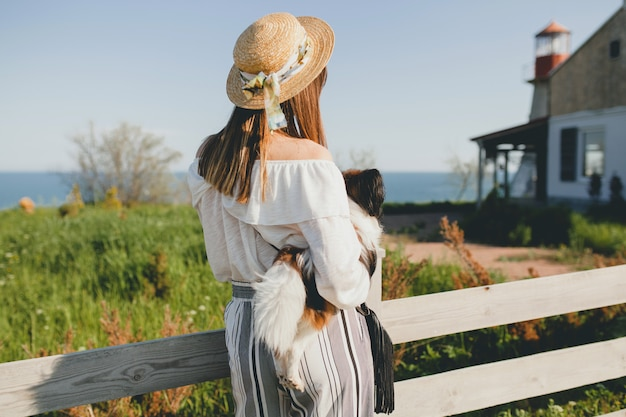 Młoda kobieta w słomkowym kapeluszu z psem przy płocie na wsi