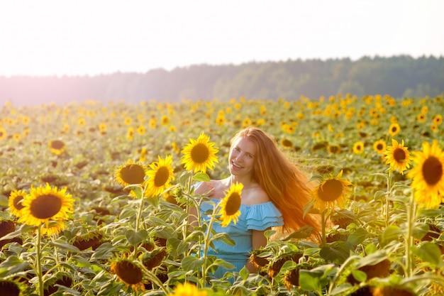 Młoda kobieta w słonecznikowe pole ma zabawy