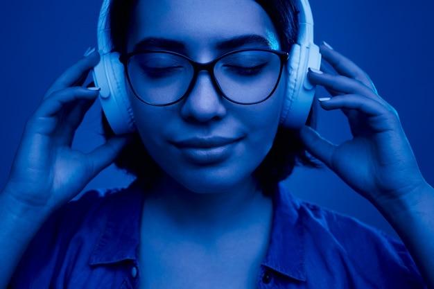 Młoda kobieta w słuchawkach ciesząca się dobrą muzyką