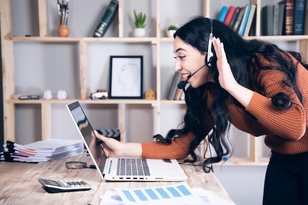 Młoda kobieta w słuchawkach mówiąc patrząc na laptopa