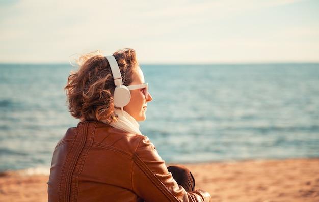 Młoda kobieta w słuchawkach na plaży