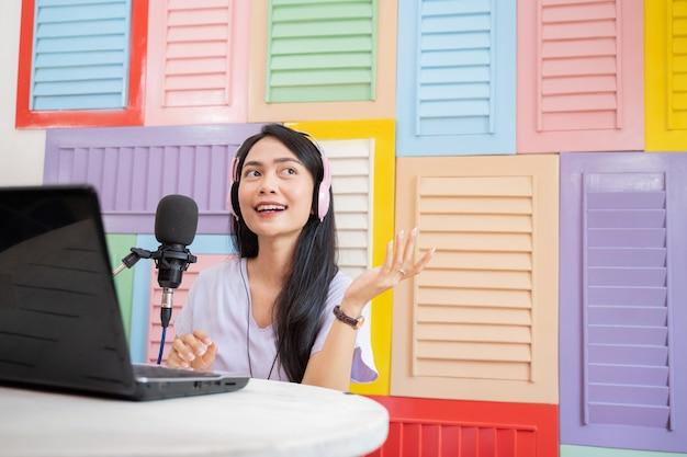 Młoda kobieta w słuchawkach rozmawiająca przed mikrofonem gestem ręki