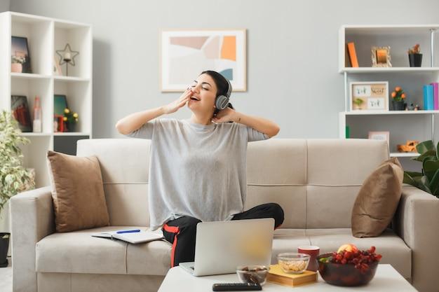 Młoda kobieta w słuchawkach siedzi na kanapie za stolikiem kawowym w salonie