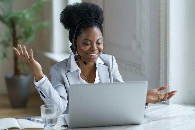 Młoda kobieta w słuchawkach siedzi przy laptopie szczęśliwa rozmowa z klientem podczas telekonferencji wideoczatu