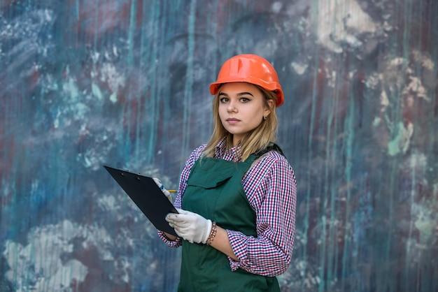 Młoda kobieta w specjalnym mundurze i cliboardzie planuje dokonać naprawy w domu