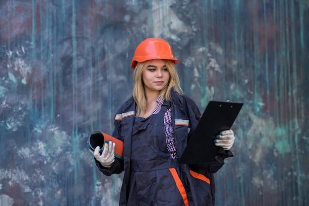 Młoda kobieta w specjalnym mundurze i tablicy planuje dokonać naprawy w domu