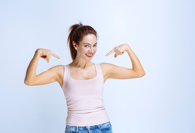 Młoda kobieta w sportowej koszuli, wskazując na siebie