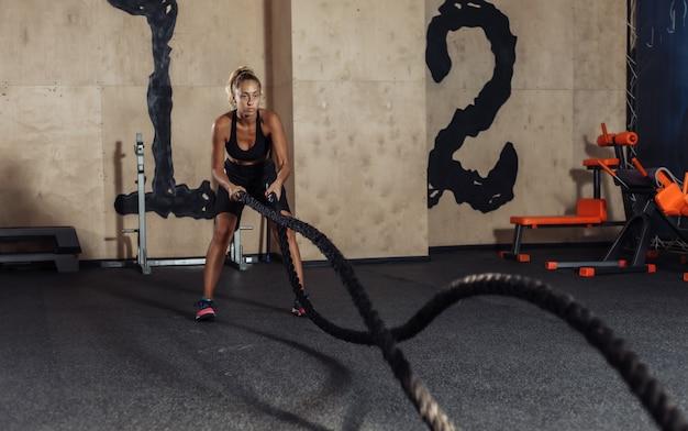 Młoda kobieta w sportowej odzieży trenuje z liną bojową na siłowni. trening funkcjonalny. pojęcie zdrowego stylu życia