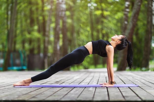 Młoda kobieta w sportowej praktyki jogi robi ćwiczenia purvottanasana lub pozie deski odwrotnej