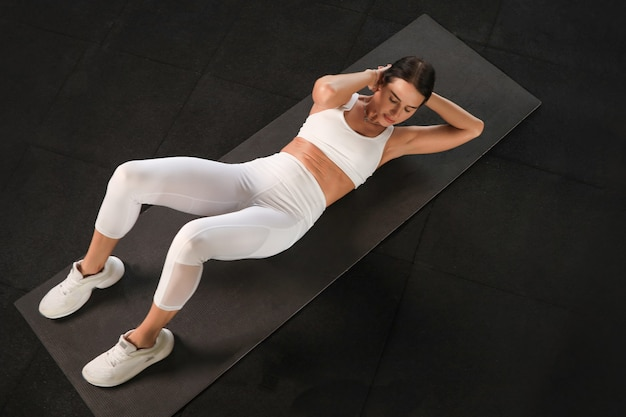 Młoda kobieta w sportowej robi brzuszki na siłowni, widok z góry.