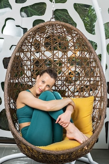 Młoda kobieta w sportowej siedzi w wiszącym fotelu