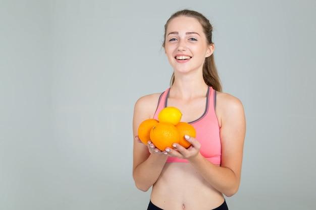 Młoda kobieta w sprawności fizycznej odzieży trzyma pomarańcz owoc i cytrynę w jej rękach, odosobnionych na popielatym