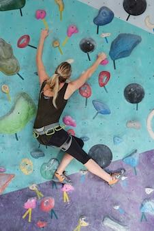 Młoda kobieta w sprzęt wspinaczkowy porusza się w górę trzymając przez sztuczne skały podczas treningu w siłowni
