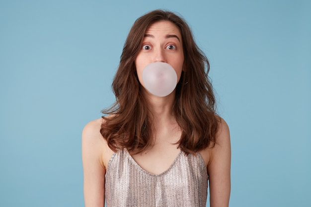 Młoda kobieta w srebrnej bluzce z gumą do żucia