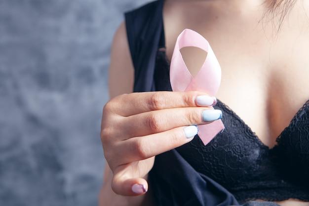Młoda kobieta w stanikach trzyma różową wstążkę. rak sutka