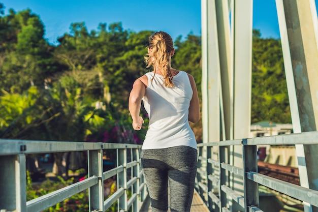 Młoda kobieta w strój sportowy działa na moście