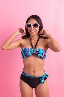 Młoda kobieta w strojach kąpielowych izolowanych na różowo