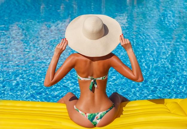 Młoda kobieta w strojach kąpielowych przy basenie