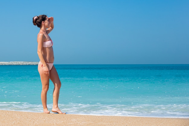 Młoda kobieta w stroju kąpielowym patrzy w dal na ocean