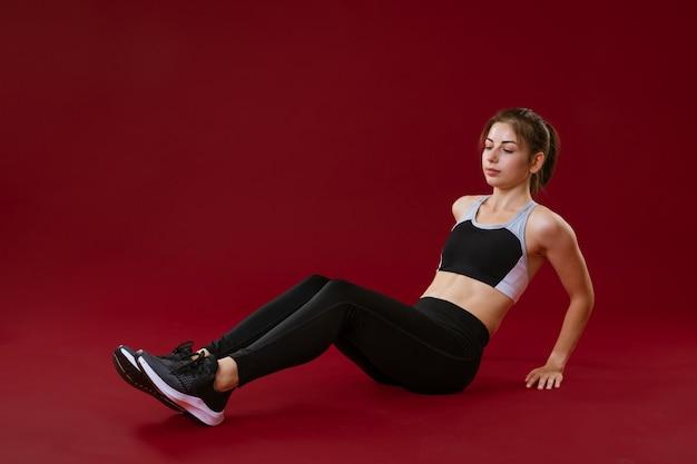 Młoda kobieta w stroju sportowym na czerwonym tle trenuje ćwiczenia brzucha