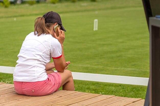 Młoda kobieta w stroju sportowym siedzi z boku pola do krokieta i rozmawia przez telefon, widok z tyłu