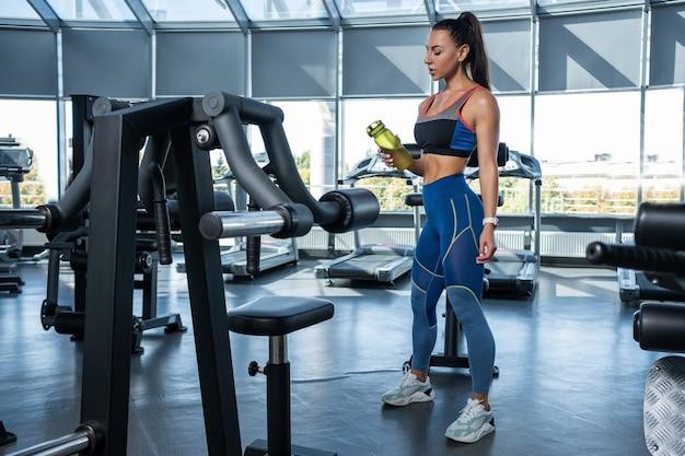 Młoda kobieta w stroju sportowym stojąca z butelką wody na siłowni