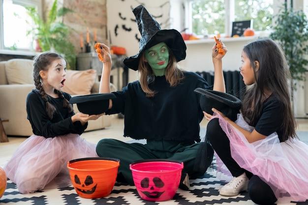 Młoda kobieta w stroju wiedźmy wkładająca smakołyki w czapki dwóch uroczych dziewczyn