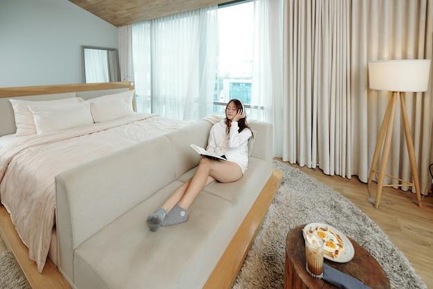 Młoda kobieta w stroju wypoczynkowym odpoczywa na sofie w domu, słucha ulubionej muzyki zamiast czytać studencką książkę na zajęcia