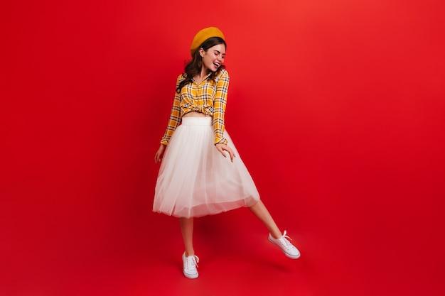 Młoda kobieta w stylowym pomarańczowym kapeluszu i jasnej bluzce tańczy na czerwonej ścianie. dziewczyna w białej spódnicy i trampkach uśmiecha się.