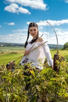 Młoda kobieta w stylu indian amerykańskich trzymających łuk i strzałę w naturze