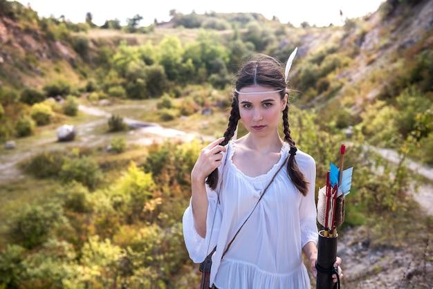 Młoda kobieta w stylu rdzennych mieszkańców ameryki z łukiem i strzałą w naturze
