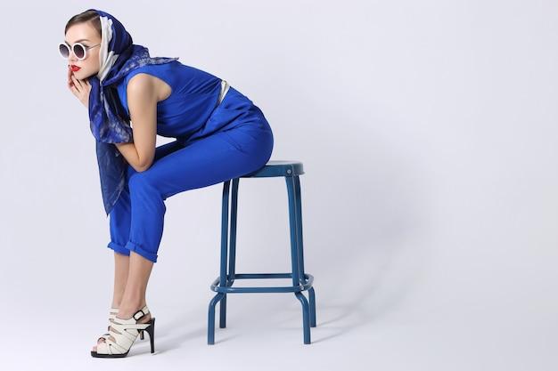 Młoda kobieta w stylu retro z okulary i jedwabny szal i niebieski kombinezon. moda retro kobieta w stylu lat sześćdziesiątych.