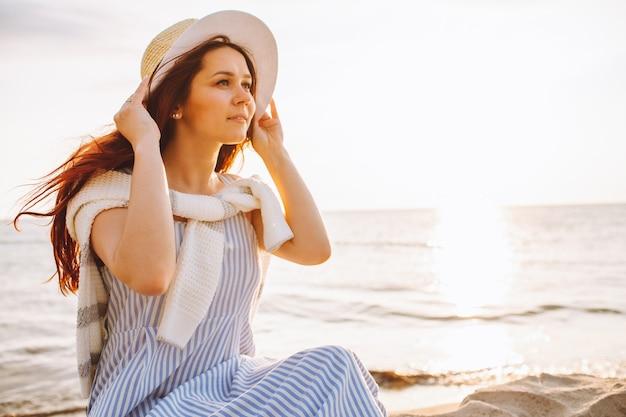 Młoda kobieta w sukience i słomkowym kapeluszu siedzi samotnie na pustej piaszczystej plaży o zachodzie słońca latem na brzegu morza i uśmiech. miejsce na wiadomość.