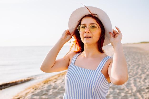 Młoda kobieta w sukience na sobie słomkowy kapelusz i żółte okulary spaceruje samotnie po pustej piaszczystej plaży o zachodzie słońca nad brzegiem morza i uśmiecha się.