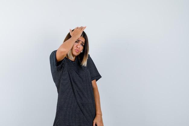 Młoda kobieta w sukience polo, trzymając rękę na głowie i niezdecydowany, widok z przodu.