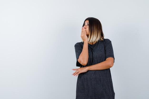 Młoda kobieta w sukience polo, trzymając rękę na ustach i patrząc zamyślony, widok z przodu.