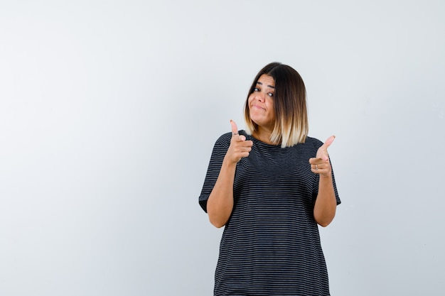 Młoda kobieta w sukience polo, wskazując na aparat i patrząc pewnie, widok z przodu.