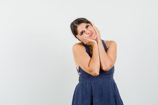 Młoda kobieta w sukience przytula twarz na dłoniach i wygląda pięknie