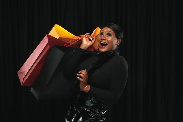 Młoda kobieta w sukience robi zakupy na czarno
