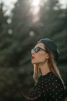 Młoda kobieta w sukience vintage czarna kropka pozowanie na zewnątrz