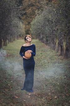 Młoda kobieta w sukience w ogrodzie jesienią trzyma dyni