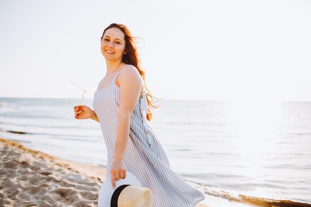 Młoda kobieta w sukience w słomkowym kapeluszu spaceruje samotnie po pustej piaszczystej plaży na brzegu morza o zachodzie słońca i uśmiecha się.