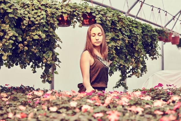 Młoda kobieta w sukience wśród kwiatów i ozdobnych roślin ampelowych w szklarni w odcieniach sepii